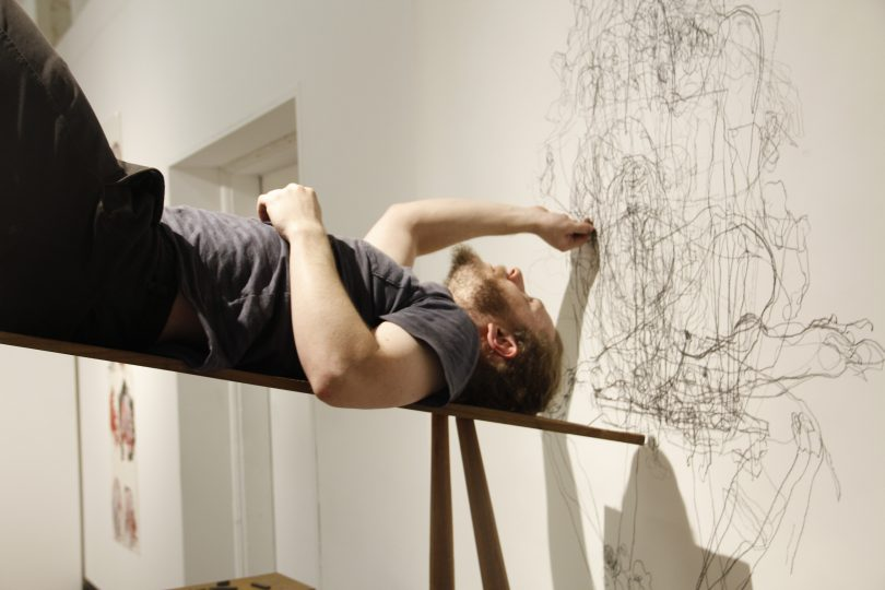 Artist Robbie Karmel lying on a bench on his back creating an abstract drawing with charcoal on wall.